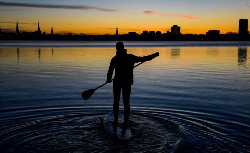 GERMANY: A paddler guides his board through the water at the Outer Alster Lake as the winter sun sets in Hamburg, northern Germany. Photograph: Axel Heimken/AFP/Getty Images