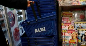 A woman picks up a basket at the Aldi store. Aldi is accusing rivals Tesco and SuperValu of working deliberately to obstruct its expansion using planning objections. Photograph: Darren Staples/Reuters