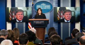 White House press secretary Sarah Huckabee Sanders looks on as US president Donald Trump delivers a statement.