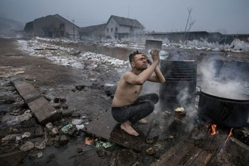 January 2017 - A man washes outdoors using a plastic bottle at a disused warehouse complex in Belgrade, Serbia. Many hundreds of refugees making their way across Europe have sought shelter from the freezing temperatures of the Serbian winter, as their journeys are thwarted by stricter border controls.  Photograph:Paul Hansen/Dagens Nyheter/ Médecins Sans Frontières