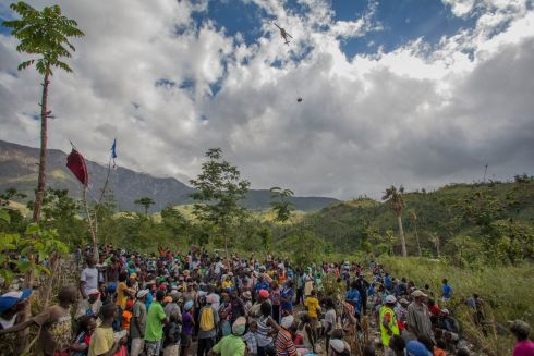 January 2017 - Residents of Bolosse, in the Haitian mountains, watch the arrival by helicopter of an MSF relief package of medical aid and building materials. MSF is conducting relief distributions in some of the most remote areas of the country following the devastation by Hurricane Matthew. Photograph: Jeanty Junior Augustin/ MSF