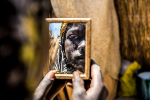 February 2017  A woman attending an MSF pre-natal clinic in Diffa, Niger, stares back at her reflection in a handheld mirror.  Photograph: Juan Carlos Tomasi/ MSF