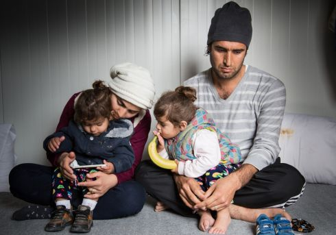 "March 2017 - Karon, 31, sits with his wife and their twin girls in a refugee shelter on the Greek island of Lesvos. The family arrived in August 2016 but have since been blocked by Greek authorities from leaving the island to continue their journey to the mainland. ""What I have seen in Iraq, I do not want my children to see it again. This is why we left our country, where everything is paralysed, everything stopped, there is no life. My true dream is that my children will live in a beautiful country, without war, without bloodshed, without any of this. This is the only thing I wish for.""   Photograph: Giuseppe La Rosa/MSF"