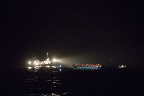 March 2017 - A wooden boat with 412 people on board, mainly from Asian countries such as Pakistan, Bangladesh and Nepal, is rescued at night by the MSF search and rescue ship, Vos Prudence and other vessels, in the Mediterranean Sea.  Photograph: Albert Masias/ MSF