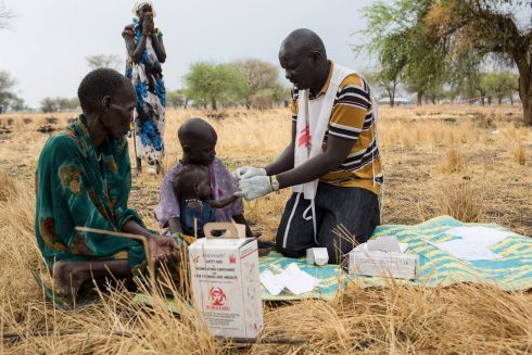March 2017 - Community health promoter, Gatbel, tests a child for malaria at an outdoor support clinic in Thaker, Leer County, South Sudan.  Photograph: Siegfried Modola/ MSF