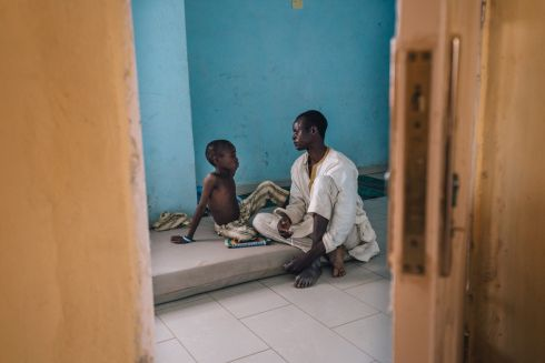 April 2017 - Zahardien Musa, a 14-year-old meningitis patients from Sokoto, Nigeria, rests on his bed with his father at the Muhammed Murtala Specialist Hospital.  Photograph: Fabrice Caterini/ INEDIZ/ MSF