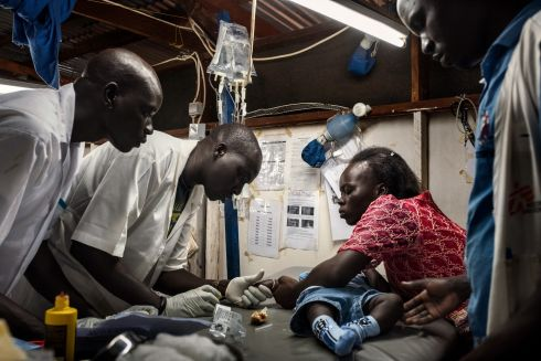 August 2017 - Doctors examine seven-month-old Bless, at the MSF hospital in Aweil, South Sudan. Bakhita (R), who is an MSF midwife in the same hospital, brought her son in suspecting he has malaria. Photograph: Peter Bauza/MSF