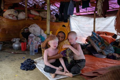 September 2017 - A Rohingya woman comforts her two sons in their tent in the Kutupalong camp in Cox's Bazar, Bangladesh. The family recently fled Myanmar joining hundreds of thousands of Rohingya who have fled across the border during episodes of violence in previous years, moving into makeshift settlements without adequate access to shelter, food, clean water or proper sanitation.   Photograph: Antonio Faccilongo/ MSF