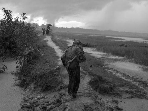 October 2017- Rohingya refugees from Myanmar, awaiting permission from Bangladeshi border guards to continue their journey to the refugee camps near Cox's Bazar, seek shelter from the monsoon rains in a rice field on the Bangladeshi side of the border with Myanmar.  Photograph: Moises Saman/Magnum Photos/ MSF