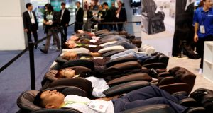 Attendees try out the Panasonic MAJ7 massage chair during. Photograph: Steve Marcus/Reuters