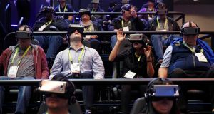 People look through Samsung Gear VR virtual reality goggles at the Samsung booth during at CES. Photograph/John Locher