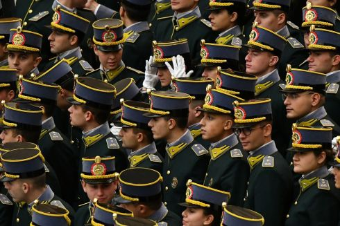A female officer from Italy's Guardia di Finanza adjusts her hat during Pope Francis's weekly audience. Photograph: Alberto Pizzolia/AFP/Getty Images
