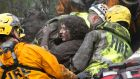 Emergency personnel carry a woman rescued from a collapsed house  in Montecito. Photograph: Kenneth Song/Santa Barbara News/Reuters