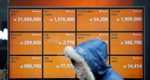 A man walks past an electric board showing exchange rates of various cryptocurrencies at Bithumb cryptocurrencies exchange in Seoul, South Korea. Photograph: Kim Hong-Ji/Reuters