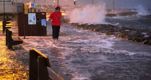 A pedestrian braving the weather on the flooded Salthill Promenade during Storm Eleanor on January 2nd, 2018. Photograph: Joe O'Shaughnessy