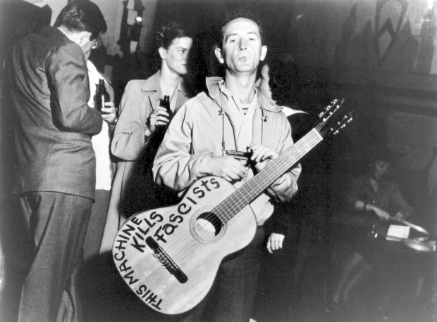 This machine kills fascists: Woody Guthrie with his guitar
