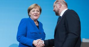 German chancellor and CDU leader Angela Merkel and SPD leader Martin Schulz shake hands in Berlin on Friday following all-night preliminary coalition talks. Photograph: Steffi Loos/Getty Images