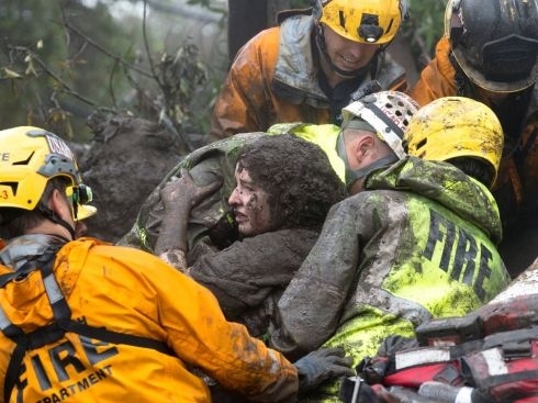 CALIFORNIA MUDSLIDES: Emergency personnel carry a woman rescued from a collapsed house after a mudslide in Montecito, California, US. Photograph: Kenneth Song/Santa Barbara News-Press via Reuters