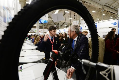 Conor Walsh from Ardscoil Rís, Dublin, explaining his project on the influence of music on cycling speed to Richard Bruton. Photograph: Alan Betson/The Irish Times