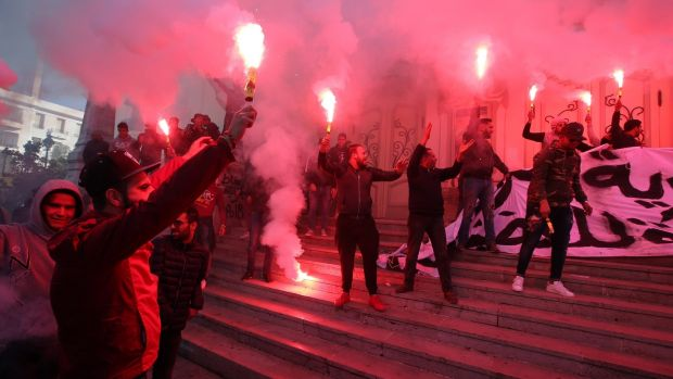 Tunisian protesters light flares and shout slogans during a celebration to mark the seventh anniversary of the uprising. Photograph: Mohamed Messara/EPA