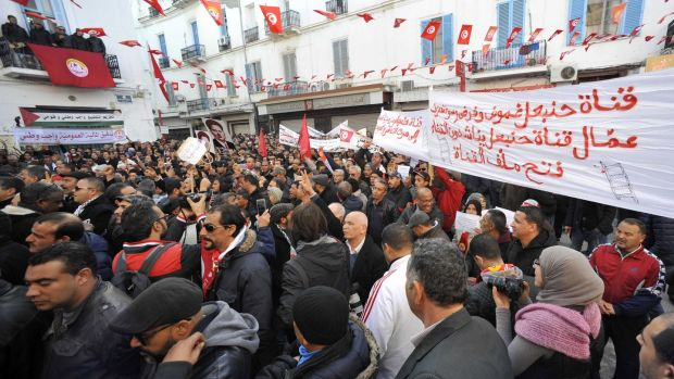 Tunisian people march with national flags during a rally to mark seven years since revolution in Tunis on Sunday. Photograph: Hassene Dridi/AP