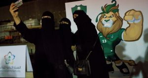 Women take a photograph outside the  match between local rivals Al-Ahli and Al-Batin in Jeddah, Saudi Arabia, on Friday. Photograph: Tasneem Alsultan/The New York Times