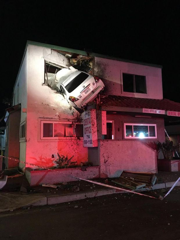 A Nissan Altima hangs from the second storey of a dental office building in Santa Ana, California, the US. Photograph: The New York Times