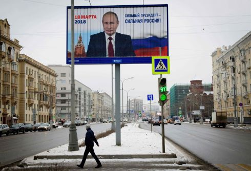 "PUTIN POWER: A pedestrian passes by a billboard with an image of Russia's president Vladimir Putin and lettering ""Strong president - Strong Russia!"" in Moscow. Photograph: Mladen Antonov/AFP/Getty Images"