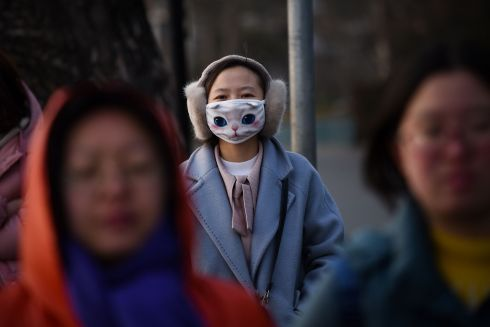 TOP CAT: A woman wears a mask with a cat pattern as she walks in Beijing. Photograph: Wang Zhao/AFP/Getty Images
