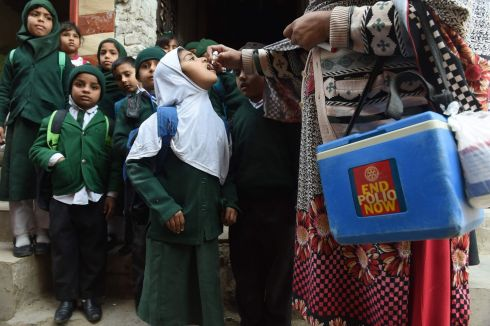 POLIO: A Pakistani health worker administers polio vaccine drops to schoolchildren in Lahore. The disease remains remains endemic in Pakistan. Photograph: Arif Ali/AFP/Getty Images
