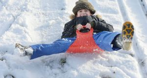 SNOW FUN Zachary O'Neill, from Ratoath, toboggans down the Hill of Tara, in Co Meath, after the countrywide overnight snow. Photograph: Alan Betson
