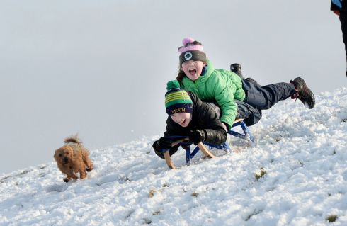 SNOW FUN Éabha Cribbins picks up speed with her brother Cillian and their dog, Rusty, at the Hill of Tara. Photograph: Alan Betson