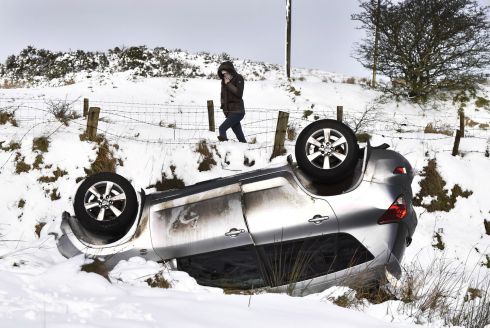 SLIPPERY OUT An overturned car in Belfast; snow has closed more than 200 Northern Ireland schools and left some roads impassable. More snow is expected on Thursday. Photograph: Charles McQuillan/Getty