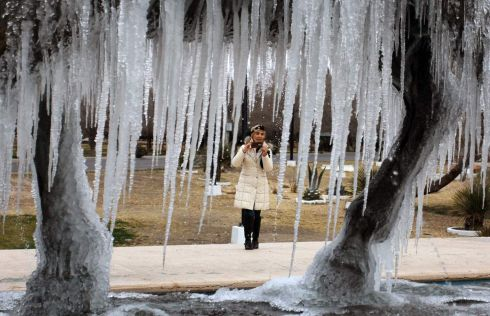 WORTH A PHOTO A woman takes a picture of an ice-covered monument during unusually cold weather in the Mexican city of Ciudad Juárez . Photograph: Herika Martinez/AFP/Getty