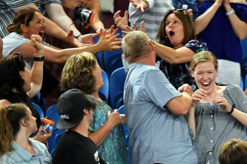 MATCH SOUVENIR Spectators catch a shoe thrown by the Ukrainian tennis player Alexandr Dolgopolov, at the Australian Open. Photograph: Lukas Coch/EPA