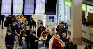 Passengers looking at displays to see if their plane will depart at Schiphol airport on Friday. Photograph: EPA