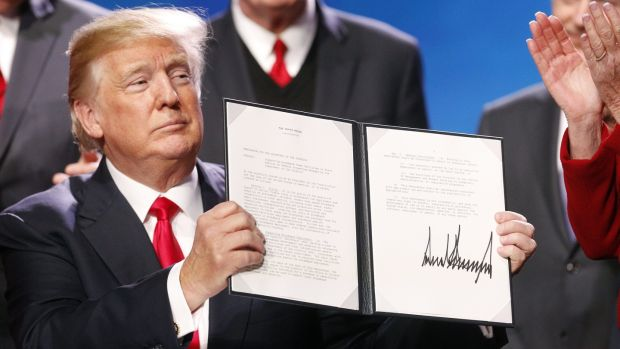US president Donald Trump displays a signed executive order, expanding rural broadband access to towers on federal lands. Trump said lower taxes and deregulation would rev up the rural economy. Photograph: Luke Sharrett/Bloomberg via Getty Images