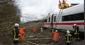 Firefighters removing trees which fell on a high-speed train near Lamspringe, northern Germany on Thursday. Photograph:  Outswen Pfortner/AFP/Getty Images