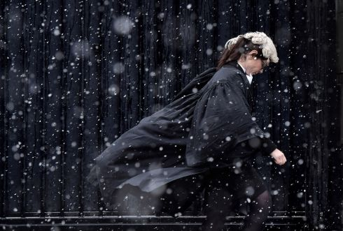 BELFAST SNOWS: A barrister makes her way into Belfast High Court through heavy snow in Belfast, Northern Ireland. Photograph: Charles McQuillan/Getty Images