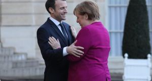 French president Emmanuel Macron welcomes German chancellor Angela Merkel at the Élysée Palace in Paris on Friday. Photograph: Ludovic Marin/AFP/Getty Images