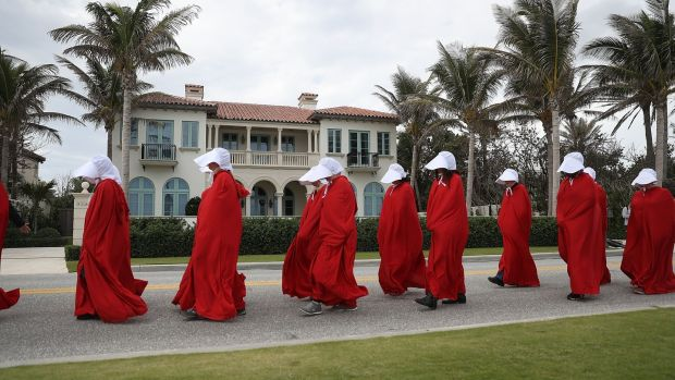 People dressed as handmaidens protest against president Donald Trump on the one year anniversary of his inauguration in Palm Beach, Florida. Photograph: Joe Raedle/Getty Images