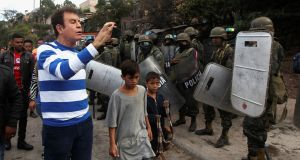Opposition candidate Salvador Nasralla, films with a mobile phone soldiers during a protest against the re-election of Honduras' President Juan Orlando Hernandez. Photograph: Jorge Cabrera/Reuters