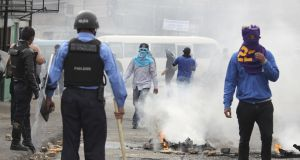 Supporters of the Opposition Alliance face off with police during a protest in Tegucigalpa, Honduras on  January 20th.  Photograph: Gustavo Amador/EPA