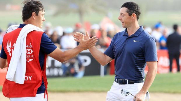 Rory McIlroy shakes hands with caddie Harry Diamond after his final round 70 in Abu Dhabi. Photograph: Andrew Redington/Getty