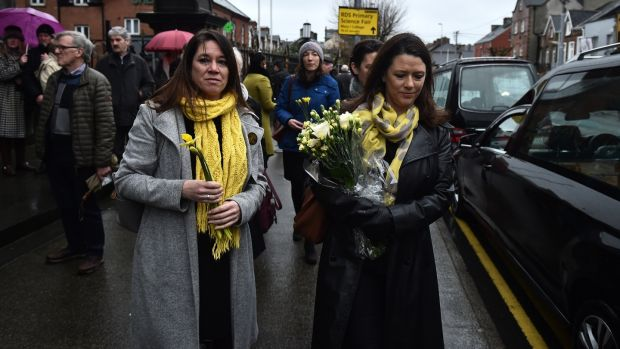 Former school classmates of the Dolores O'Riordan carry yellow flowers to signify sunshine as the late singer lies in repose in St Joseph's Church in Limerick. Photograph: Charles McQuillan/Getty