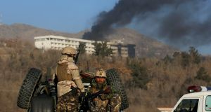 Afghan security forces keep watch as smoke rises from the Intercontinental Hotel in Kabul on which a Taliban attack left many dead. Photograph: Omar Sobhani/Reuters
