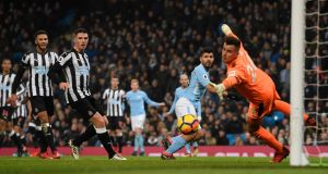 Manchester City's   Sergio Agüero scores the opening goal past Newcastle's Karl Darlow at Etihad Stadium on Saturday. Photograph:  Stu Forster/Getty Images