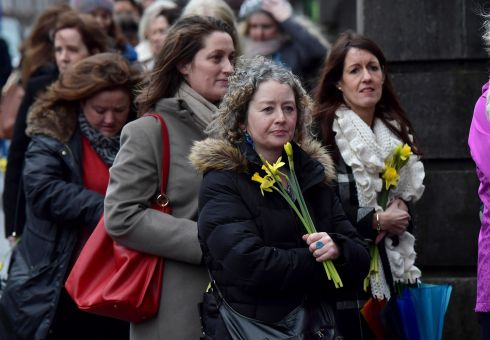 LOVING MEMORY: Former school classmates of Dolores O'Riordan carry yellow flowers to signify sunshine as mourners and members of the public pay their respects to the late singer as she lays in repose inside St Joseph's Church in Limerick. Photograph: Charles McQuillan/Getty Images