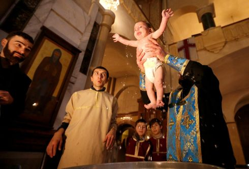BAPTISMAL CEREMONY: A baby is baptised during a ceremony at the Holy Trinity Cathedral in Tbilisi, Georgia. Photograph: David Mdzinarishvili/Reuters