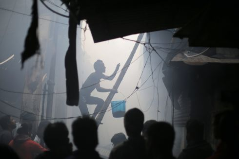 WE'RE GOING TO NEED A BIGGER BUCKET: A shop owner climbs a ladder with a bucket of water as he tries to extinguish a fire that broke out at local market in Calcutta, India. According to media reports, 20 fire engines were deployed to the site, and it took more than 12 hours for the firefighters to bring the blaze under control. The market was evacuated and two men died. Photograph: Piyal Adhikary/EPA